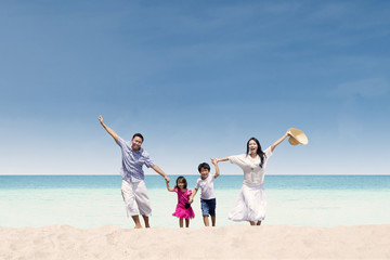 Happy family running at beach
