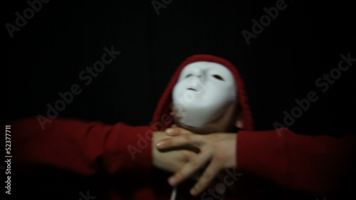 Insane masked man over dark background