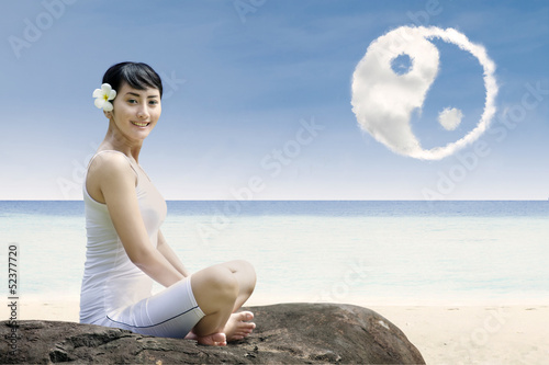 Happy girl and ying yang cloud at beach