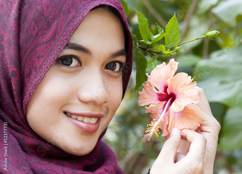 Young muslim woman holding a red hibiscus flower
