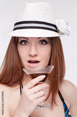 girl in a hat holding a glass near the lip,