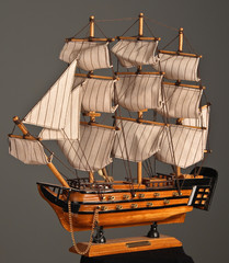 Model sailboat on a gray background.