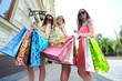 three young women with shopping bags