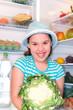 Mädchen holt Blumenkohl aus dem vegetarischen Kühlschrank