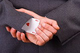 Businessman with ace card hidden under sleeve.