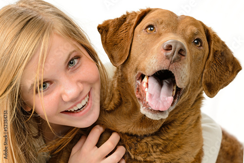 Adolescent girl embracing her golden retriever