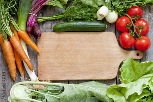 Many fresh organic vegetables and empty cutting board background