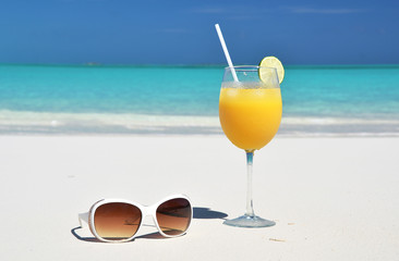 Orange juice and sunglasses on the beach. Exuma, Bahamas