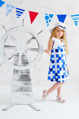 Little girl in fashion dress next to decorative steer wheel