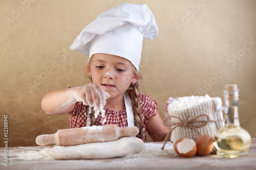 Little girl stretching the cookie dough