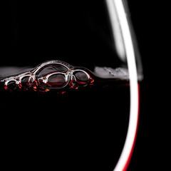 Rot wein glas mit blasen auf schwarzem Hintergrund