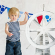 Cute little sailor boy holding a steer wheel