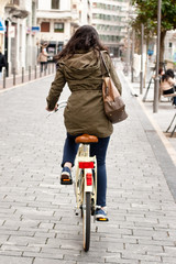 Woman cycling down the street