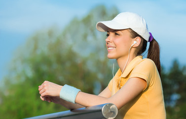 Happy young sports woman hear music