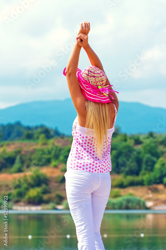 Pretty young woman with arms raised