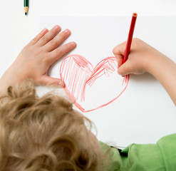 Fair child drawing heart, metaphor for love