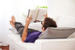 Young man stretching comfortably on couch and reading a book