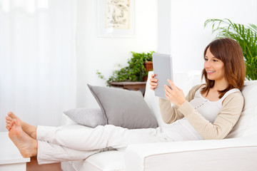 Young woman working with a digital tablet at home