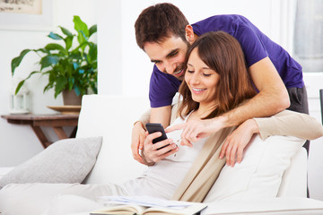 Young couple looking a smartphone at home