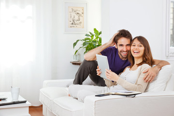 Young couple with digital tablet at home