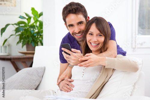 Young couple with a smartphone at home