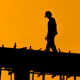 Silhouette of construction workers on scaffold working under a h poster