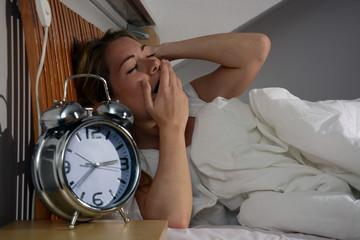 Junge Frau liegt wach im Bett