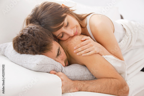 Portrait of a young couple sleeping on bed