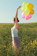 woman in a field under a clear sky with colored balloons