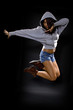 latina dancer wearing a hoodie jumping.