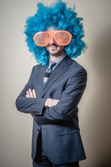 funny businessman with big orange glasses and blue wig