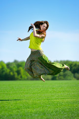 Young woman jumping on a green meadow