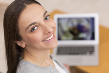 Woman on sofa with her laptop face camera