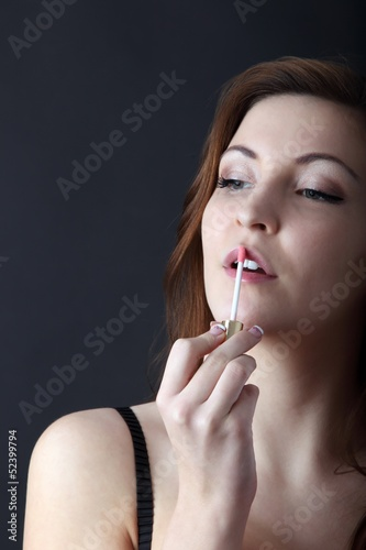 beautiful young woman applying lip gloss