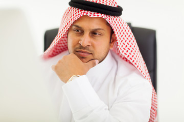 arabic businessman looking at computer screen