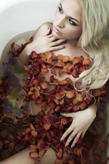 Beautiful sexy blond woman in water with flowers