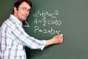 Lehrer schreibt Geometrieformel an Tafel
