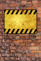 a brick wall with a warning sign
