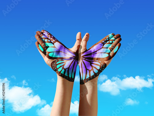 canvas print picture Hand and butterfly hand painting, tattoo, over a blue sky