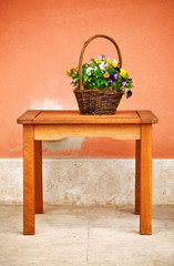 basket with flowers and green leaves on wooden table