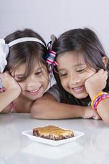 Dos niñas sonrientes ven un apetitoso postre