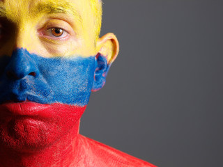 Man face painted with colombian flag, sad expression.
