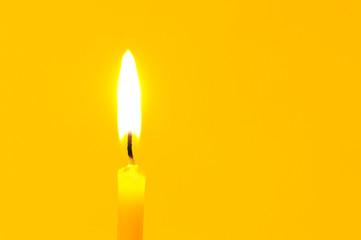 Burning candle on yellow background