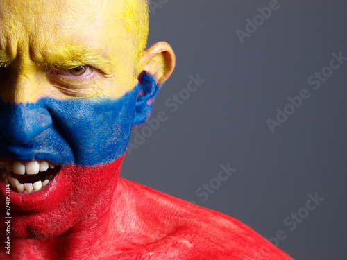 Man face painted with colombian flag, angry expression.