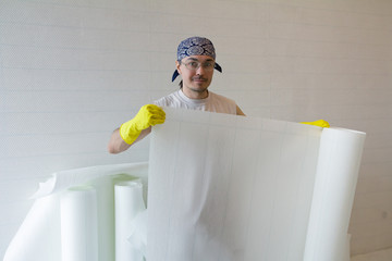 Young worker holding roll of  wallpaper