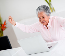 Happy elder woman with arms up
