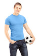 Young handsome man holding a soccer ball
