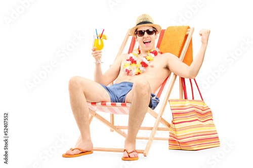 Happy young man enjoying a cocktail and sitting on a beach chair