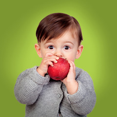 Adorable baby eating a red apple