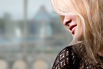 Close-up portrait of a beautiful blonde in a profile on a blurre